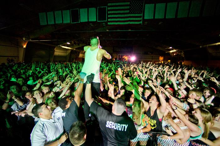Macklemore stands on a barrier to get closer to the audience in the Field House. PHOTO: BY MEGAN HAMAN