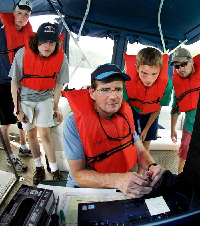 Prof. Mike McCormick maneuvers the remotely operated vehicle looking for a spot to collect bacteria samples from Green Lake. Looking on are Kevin Boettger, Matt Brzustoski, Rob Clayton and Daniel Lichtenauer. PHOTO: BY NANCY L. FORD