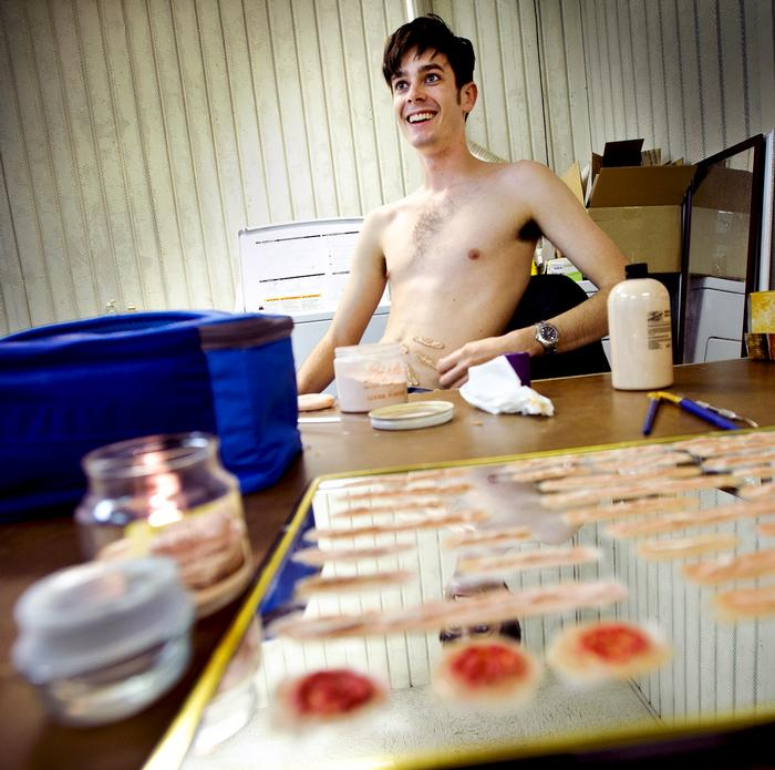 Charlie Wilson '16 applies fake scars and cigar burns to his body. PHOTO: NANCY L. FORD