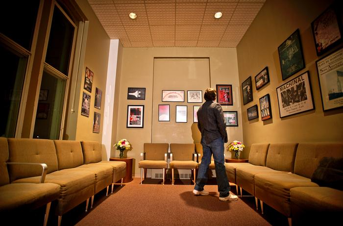 John Schuette looks at posters hanging on the wall in the lobby during a reception after the final show. PHOTO: NANCY FORD
