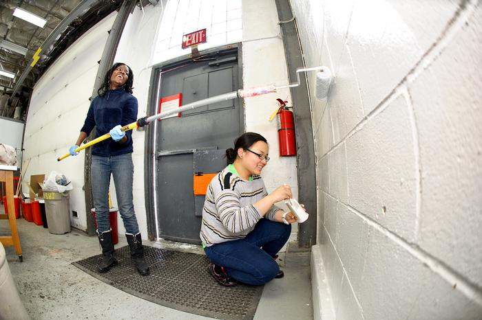 Latasha Thomas '13, left, and Debbie Chen '13 white-wash the walls at Sculpture Space.  PHOTO: BY NANCY L. FORD