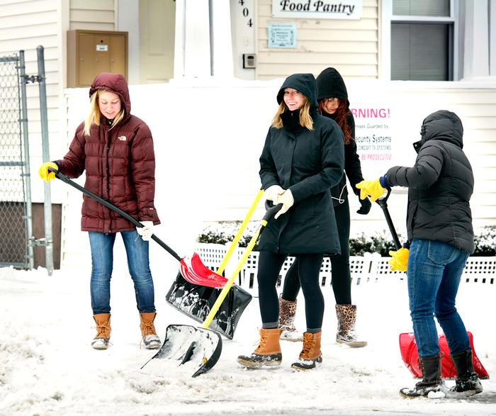 From left, Annie Phillips '13, Samantha Schwartz '13, and Sarah Mehrotra '13 (back to camera) shovel snow as they volunteer for the JCTOD JP. PHOTO: BY NANCY FORD