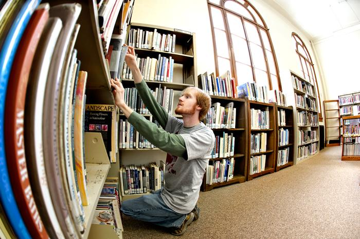 Bret Turner '13 organizes and refiles books in the Utica Public Library. PHOTO: BY NANCY FORD