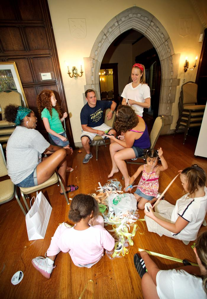 Naomi Tsegaye '16 (green head scarf) Nick Gustaitis '16, center sitting, and Carina Elfving '16, work with children during Outreach Adventure at the Rome Community Arts Center. PHOTO: BY NANCY FORD