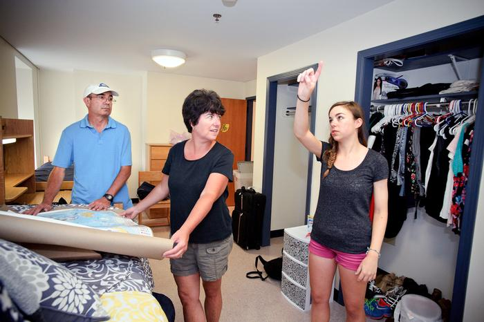 Rachel Alatalo '18, and parents, decide where to hang her poster of the world map in her dorm room in North Residence Hall. PHOTO: REBECCA SHEETS