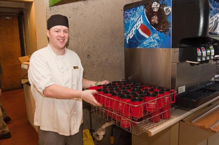Bon Appetit employee Bryan Drummond brings out another load of recyclable mugs in the McEwen dining hall