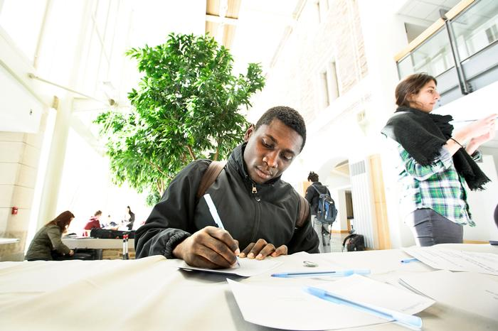 Sadiq Abubakar '15 signs a thank you card. PHOTO: NANCY FORD