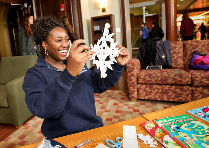 Maybelline Acquaye '14 reacts with surprise after unfolding a paper snowflake she created.  PHOTO: BY NANCY FORD