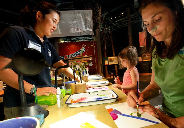 Zoe Tessler '16 left  helps a young artist paint butterflies at the Wild Center. PHOTO: NANCY L. FORD