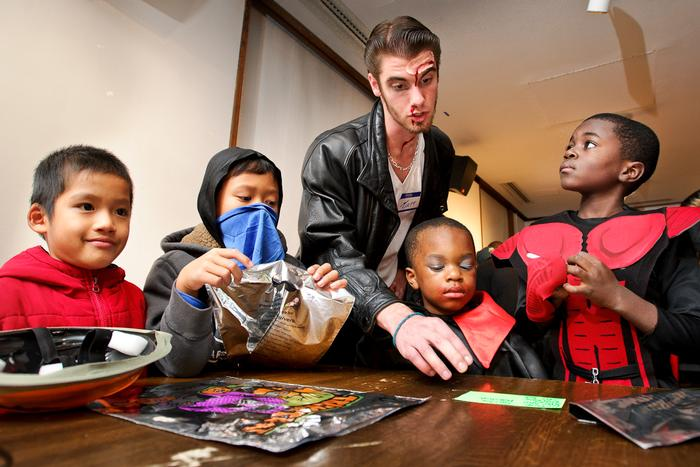 Matt Reinemann '17 helps helps superheroes and goblins during Trust Treat. PHOTO: BY NANCY L. FORD