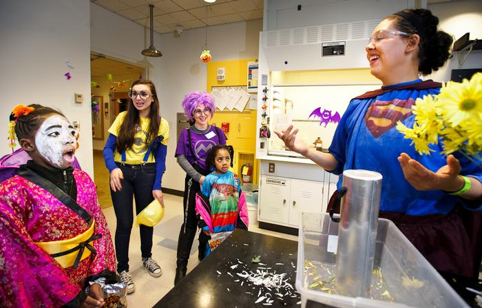 Laura Rivera '16 dazzles trick-or-treaters with a shattered flower experiment in the science lab. PHOTO: BY NANCY L. FORD