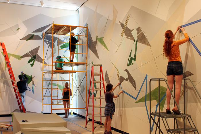 Students help artist Danielle Tegeder complete a 70-foot wall drawing in the Wellin Museum of Art. PHOTO: BY VICTORIA LIN '15