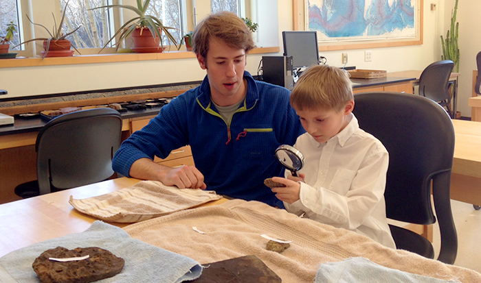 Colyer Woolston '14 and Clinton first grader John Musante examine fossils in the lab.