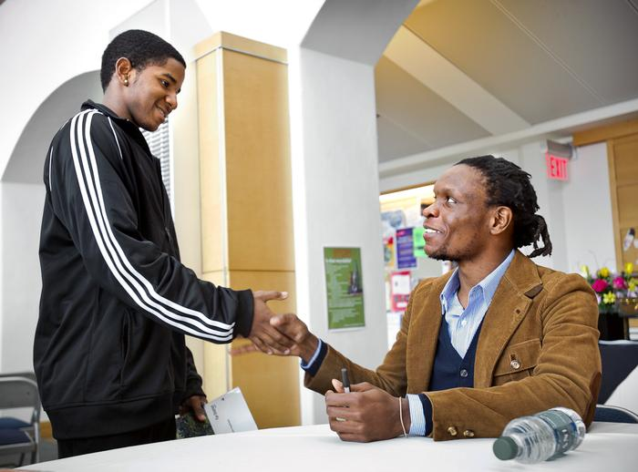 Jamaican Poet Ishion Hutchinson shakes hands with Arthur Williams '16, after signing a copy of his book.  PHOTO: NANCY L. FORD
