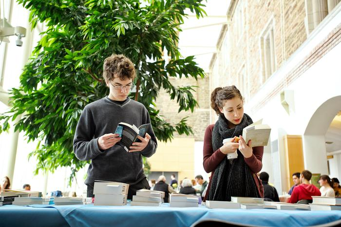 Nate Goebel '15 and Kina Viola '14 look through books during the international Book Fair. PHOTO: NANCY L. FORD