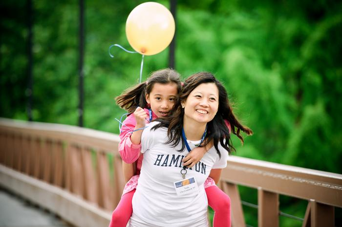 Yully Cha Leonardi '97 carries her daughter, 6-year-old Camen across the bridge to watch the Reunion Parade. PHOTO: BY NANCY FORD