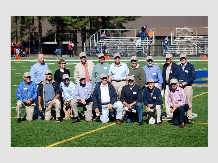 Members of the Class of 1963 football team during halftime with President Stewart and Jon Hind '80.