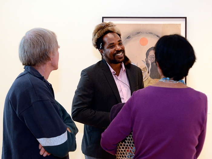 Los Angeles-based artist Frohawk Two Feathers speaks with alumni at the opening reception.