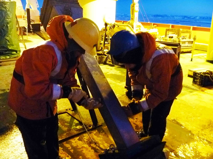 Nadine Orejola (Montclair State University) and Manique remove the panels from a 1.5 m Kasten Core on the aft deck of the Palmer. The core is brought onto deck, cleaned and then brought into the lab.
