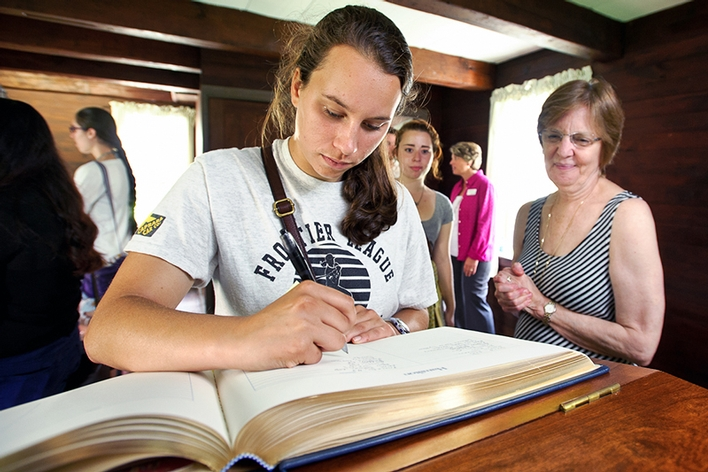 President Joan Hinde Stewart looks on as Catherine Lyndaker &apos;18 signs the College Register in Kirkland Cottage.<br />Photo: Nancy L. Ford