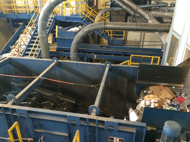 To begin post-sort, large rotating disks separate cardboard into a separate conveyer belt, leaving paper, mixed papers, glass, and plastic on the conveyer belt.