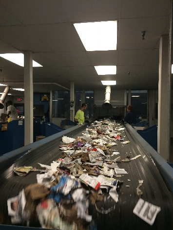 Next, sorters pull out leftover cardboard and trash before another set of rotating disks separate paper from the mixed recyclables.