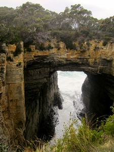 An ocean view through an archway was formed when waves eroded out a cave, causing the roof to collapse.