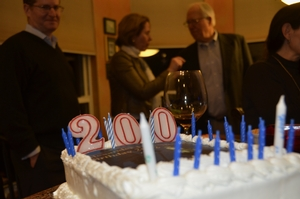 A very special cake delineated the bicentennial birthday. In the background, Ron Seaman H'53 regales Susan Skerritt, K'77 with stories.