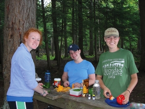 Alexandra Orlov '13, Elizabeth Scholz ' 13 and Anna Zahm '13 rustle up some grub on the trail during the Adirondack outing that kicked off their fall 2009 Adventure Writing class.