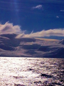 A glacier in the northern Gerlache Strait. Glacial meltwater conduits (glistening) form at high elevation and travel down-gradient where they percolate into crevasses and refreeze; something that was not observed decades ago.