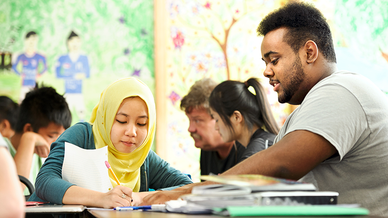 Christopher Rogers '13, right, works with refugee Mi Twe at the Mohawk Valley Refugee Center teaching her to read and write English.
