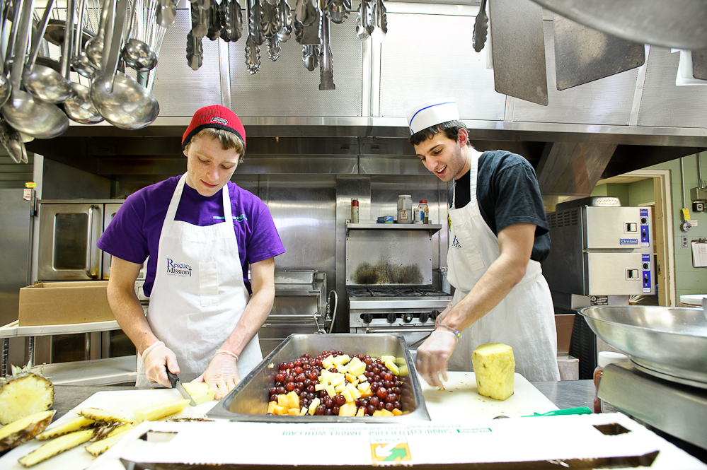 Kurt Eyerer '15, left, and Andrew Dubowitz '13 cut up fruit for dinner service as they volunteer at the Rescue Mission of Utica as part of Hamilton Serves