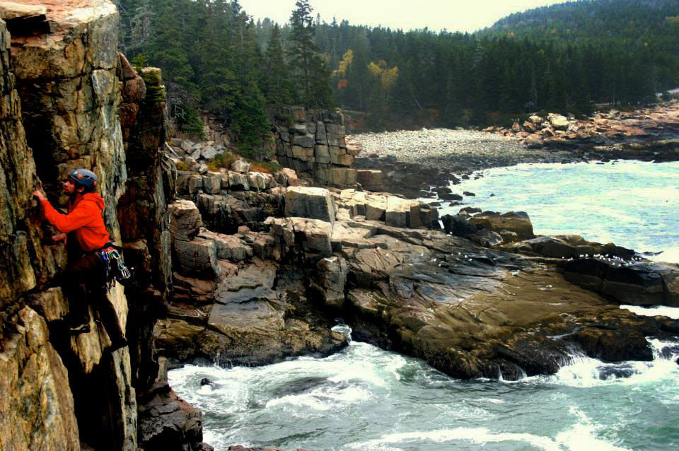 John Pikus '16 scales a cliff above the crashing ocean in Acadia National Park.