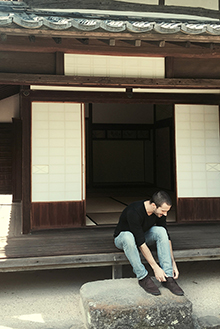 Alex Benkhart '11 laces up after taking his shoes off to walk through a former samurai residence in the town of Kitsuki, Japan.