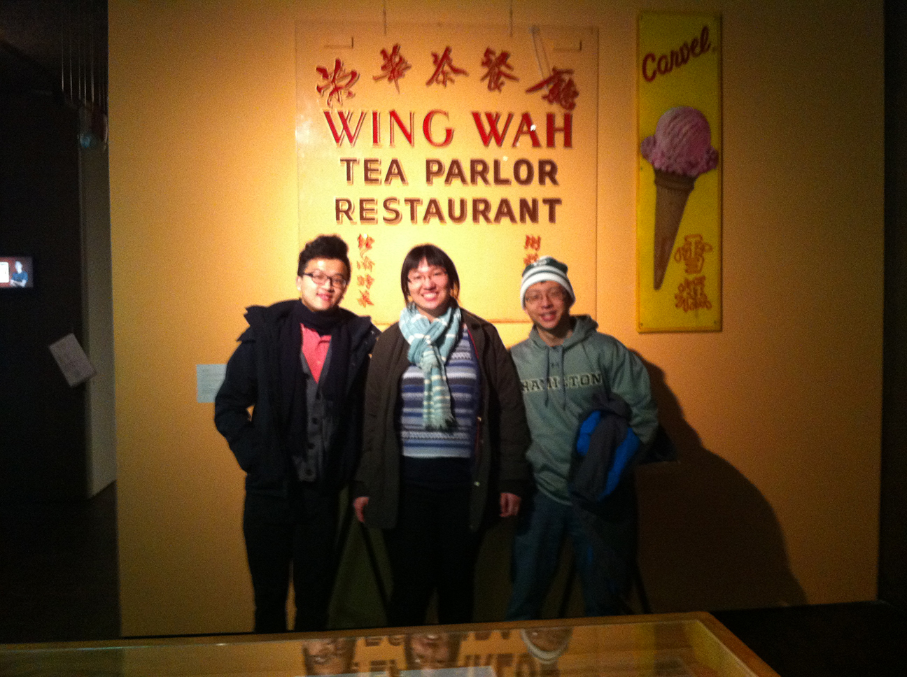Sitong Chen '16, Jessica Tang '16, Sterling Xie '16 stand in front of a sign for a tea shop.