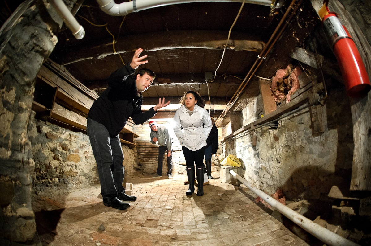 Assistant Professor of Anthropology Nathan Goodale gives Heidi Mendez '18 and other students in his archaeology class a tour of the root cellar at the house.