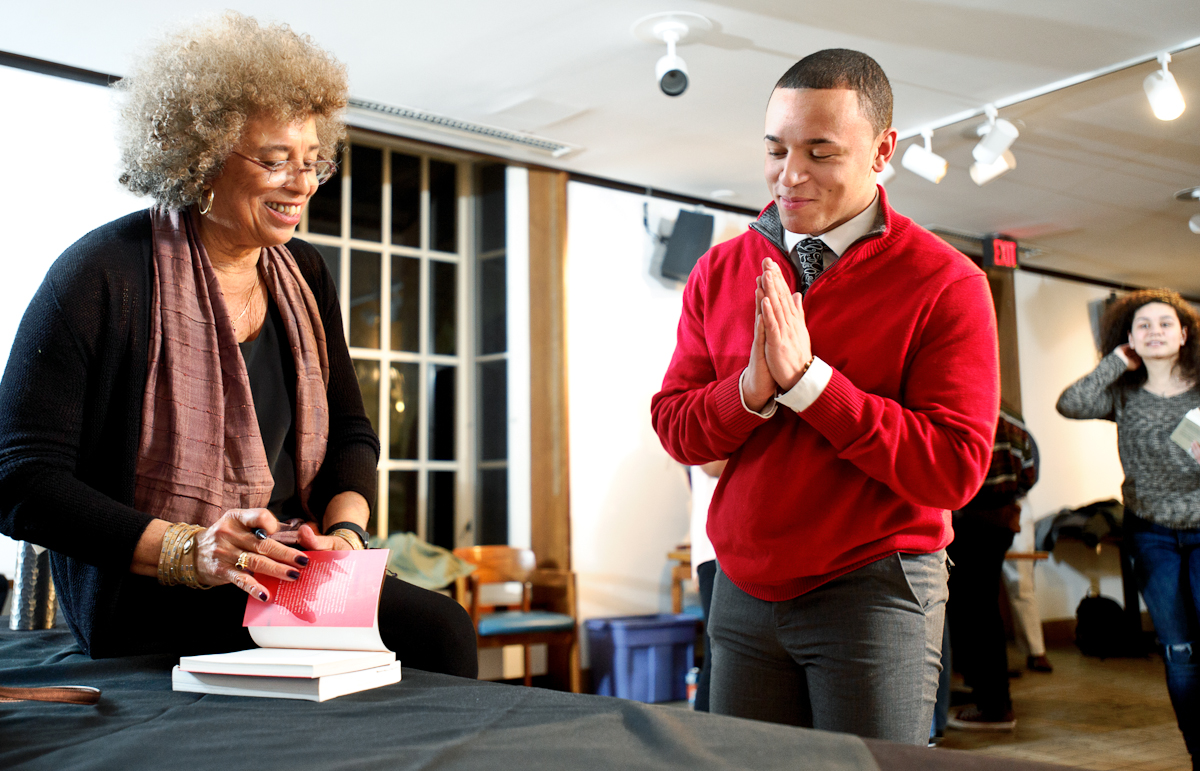 Angela Davis autographs a copy of her book for Marquis Palmer '18 in the Hub.