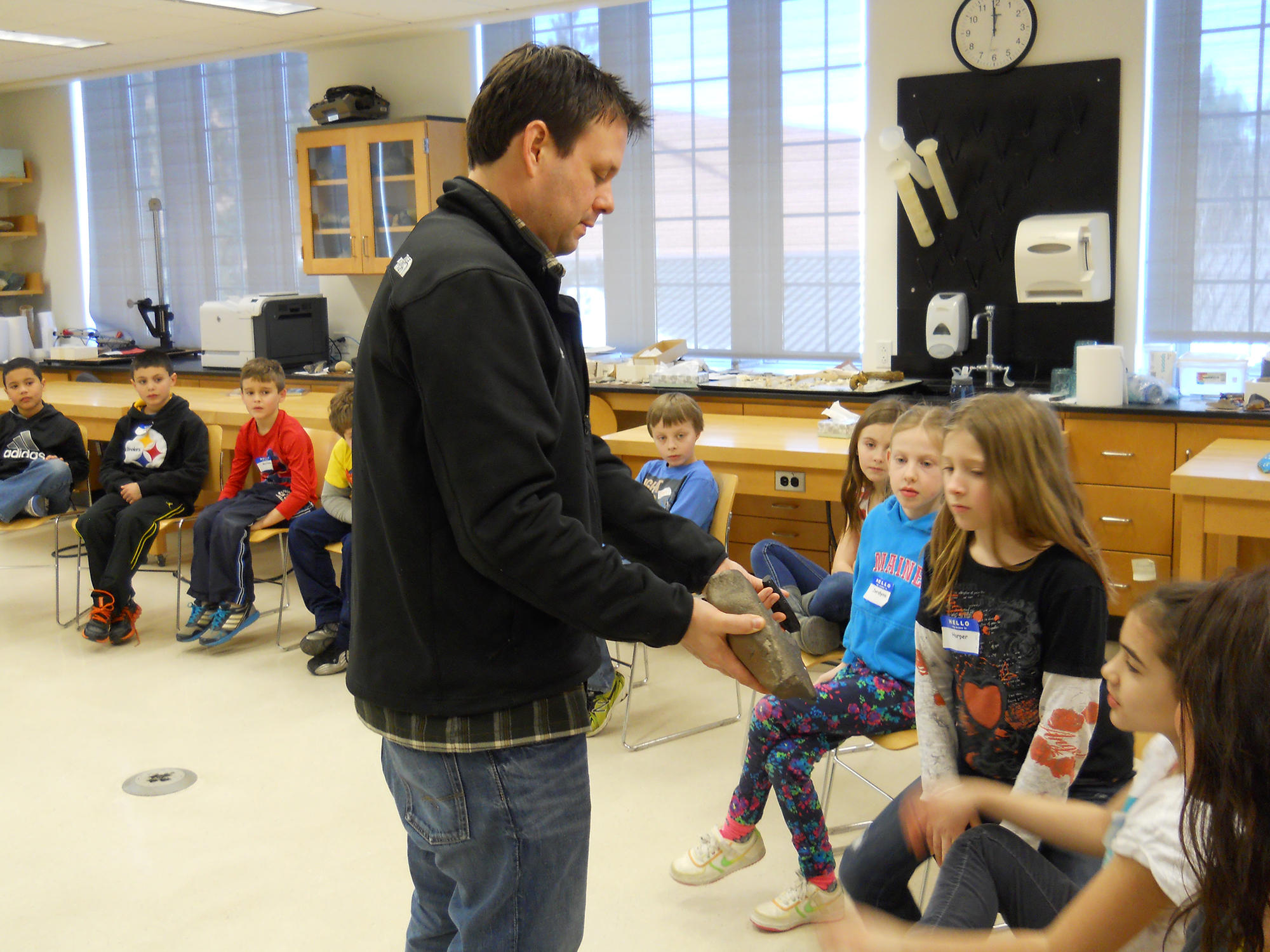 Anthropology professor Nathan Goodale shows the children igneous (volcanic) rocks called obsidian and basal.