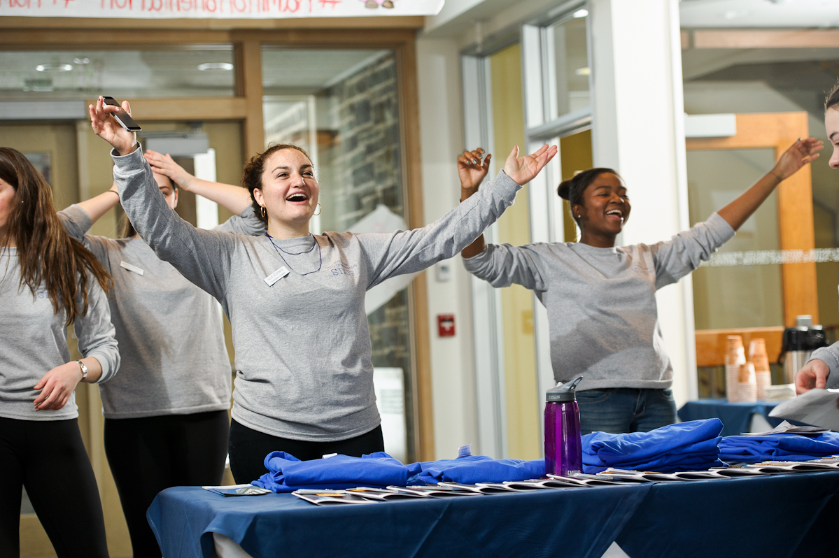 Orientation leaders Allie Goodman '15, left and Geleece Brady '16, right, raise their arms to welcome January first-year admits to campus in the lobby of Sadove Center