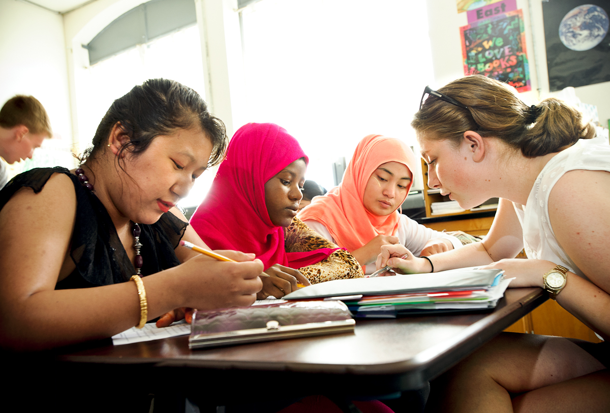 From left Sak Maya Rai, Asha Ahmed, and Cho Cho Win get a reading lesson from Hamilton alumna Sidika Kajtezovic '14,