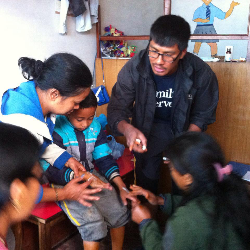 In Nepal, Ujjwal Pradhan's '15 brother, Dr. Umesh Pradhan, right, provides medical care to victims from the neighborhoods of Balaju.