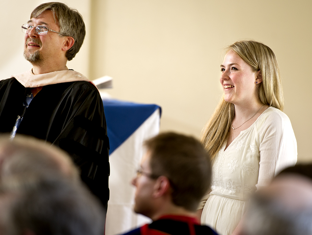 Riley Stepnick '12 with Professor of  Music Sam Pellman listens to her song performed by the Choir at Class & Charter Day.