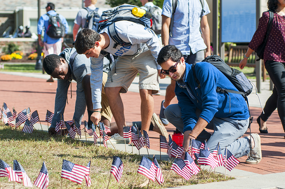 Students place flags along Martin's Way.