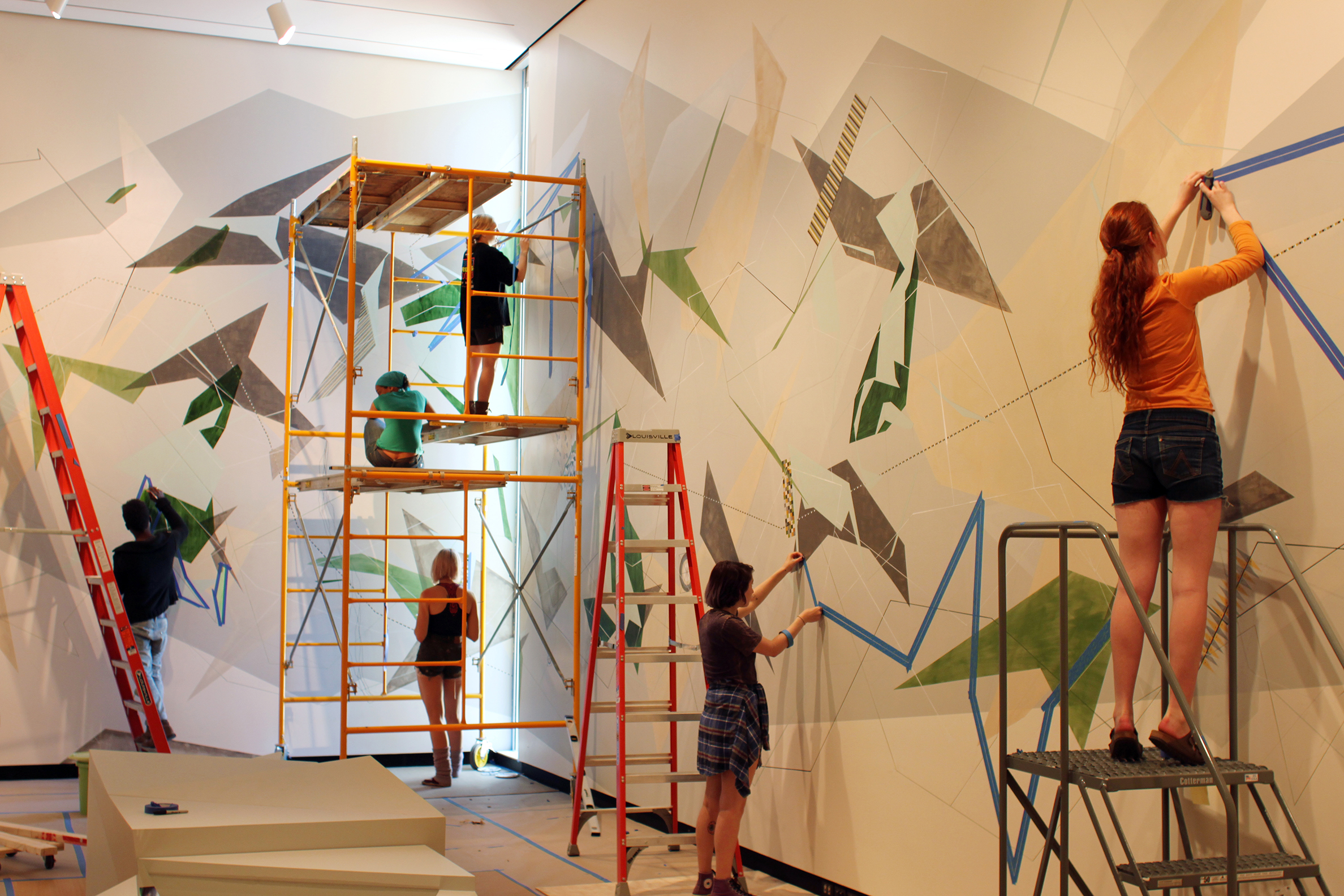 Students help artist Danielle Tegeder complete a 70-foot wall drawing in the Wellin Museum of Art.